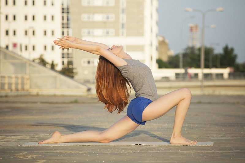 Woman doing yoga in urban environment